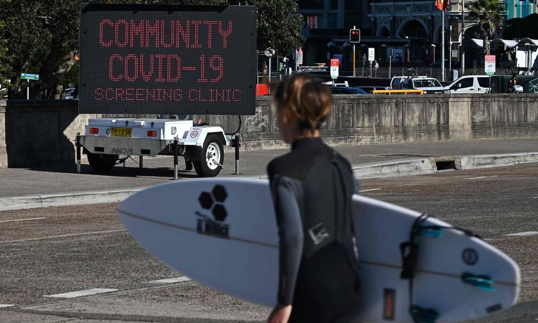 Surfista passa por uma placa para uma clínica de testes COVID-19, em Bondi Beach, Sydney Foto: STEVEN SAPHORE / AFP