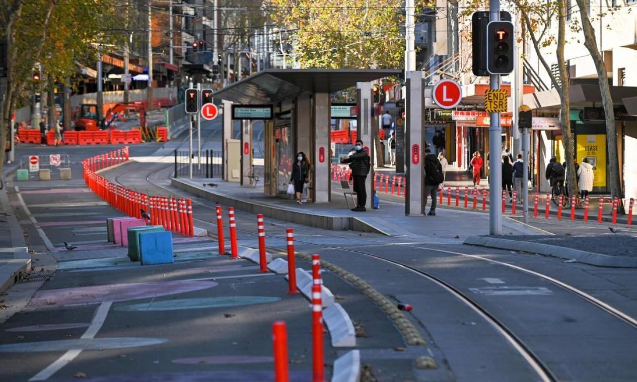 Pessoas esperam por um bonde no distrito comercial central vazio em Sydney Foto: STEVEN SAPHORE / AFP