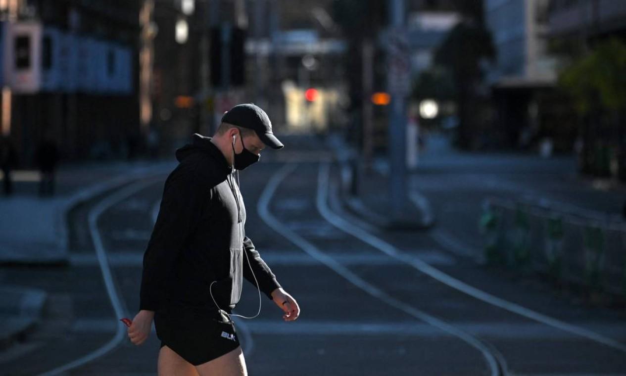 Homem usando máscara cruza os trilhos do bonde no distrito comercial central vazio de Sydney Foto: STEVEN SAPHORE / AFP