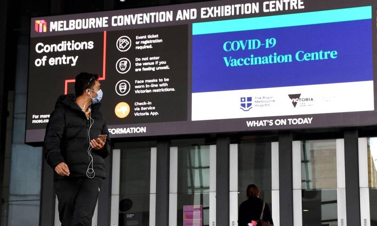 Homem passa por um centro de vacinação Covid-19 em Melbourne Foto: WILLIAM WEST / AFP