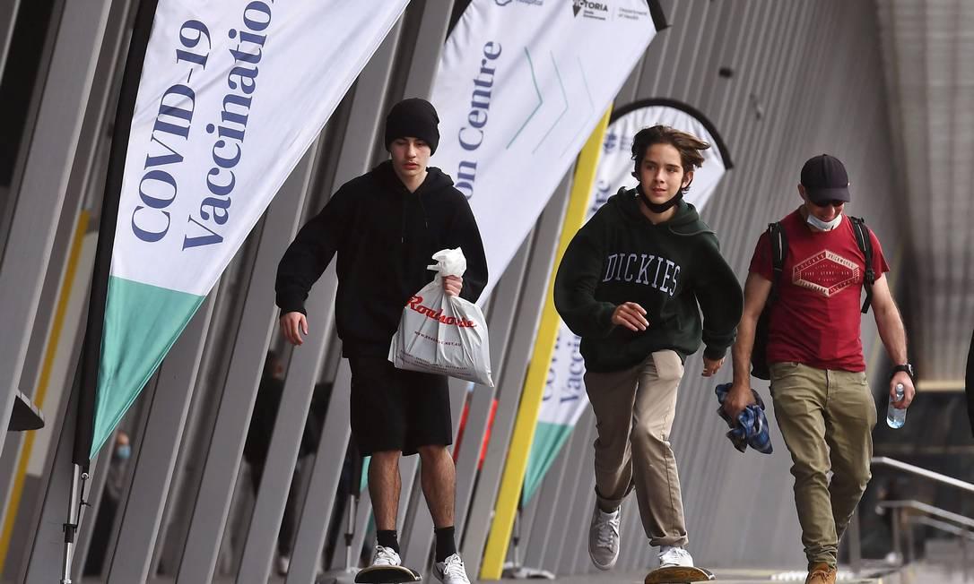 Jovens andando de skate lockpassam por um centro de vacinação Covid-19 em Melbourne Foto: WILLIAM WEST / AFP