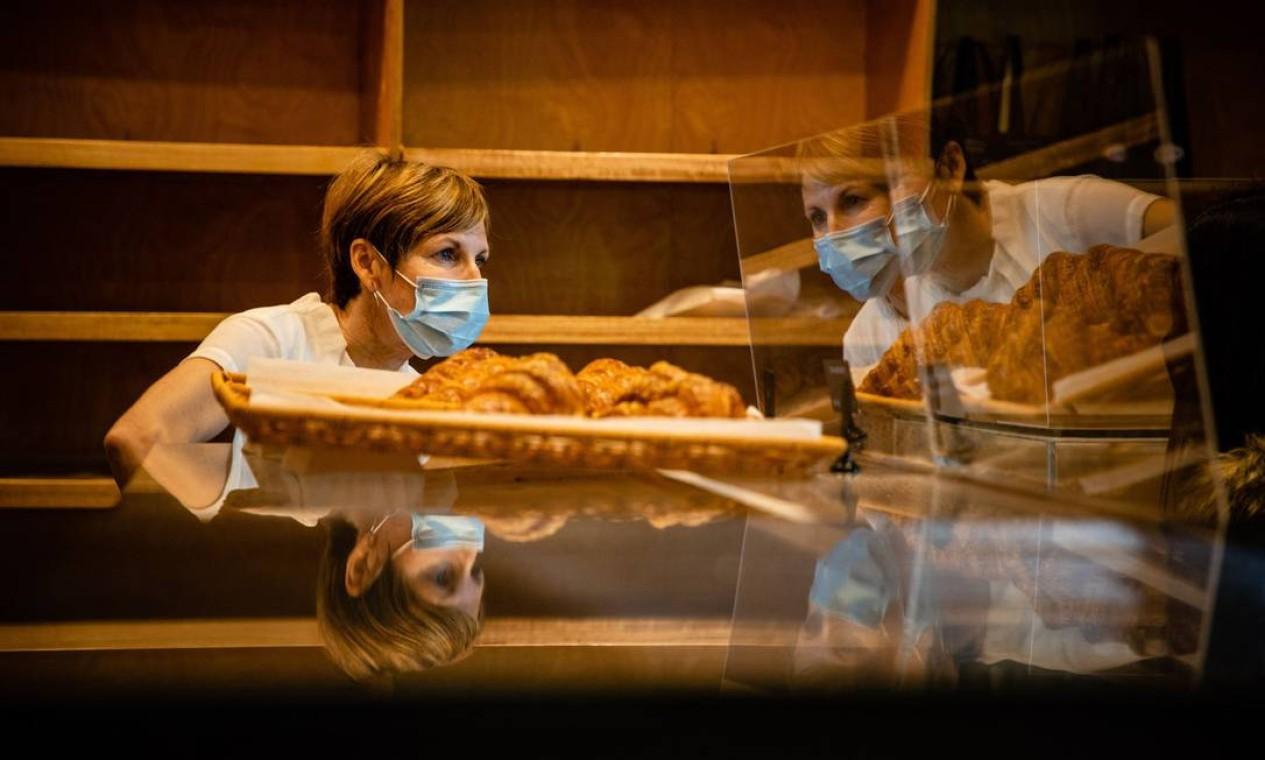 Virginie Delamare usa uma máscara facial enquanto atende um cliente em sua padaria Kangaroo Point em Brisbane Foto: PATRICK HAMILTON / AFP