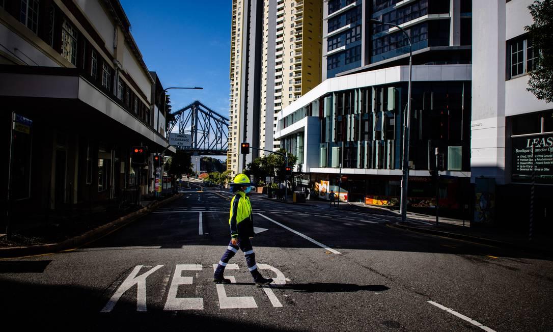 Leonela Gonzalez, trabalhadora de controle de tráfego, atravessa uma rua deserta em Brisbane Foto: PATRICK HAMILTON / AFP