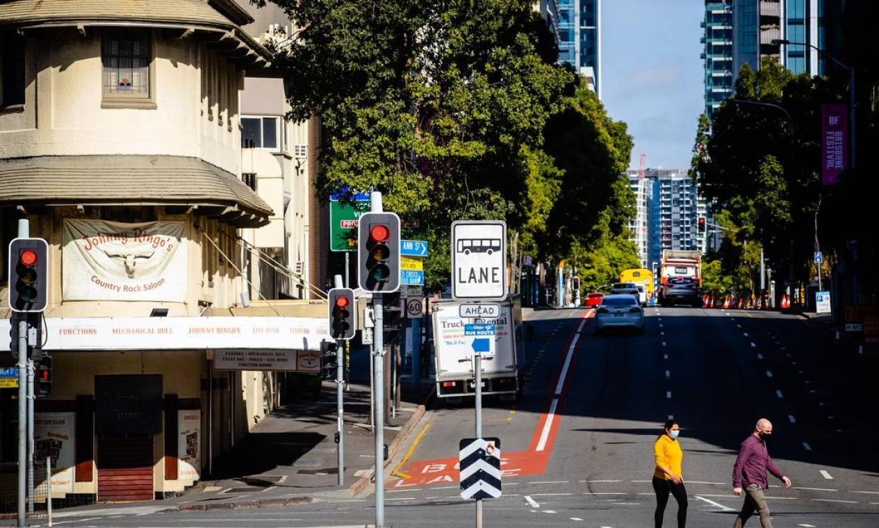 Os pedestres cruzam rua quase deserta em Brisbane Foto: PATRICK HAMILTON / AFP