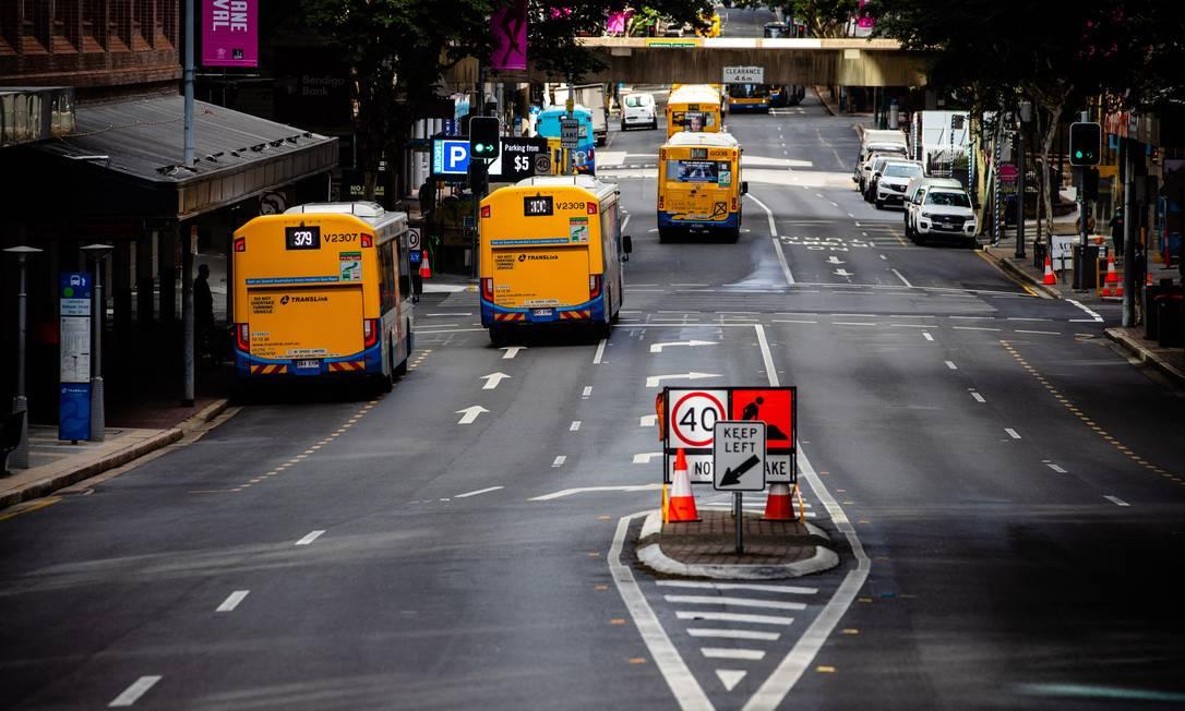 Os ônibus passam ao longo de uma rua em Brisbane, enquanto a cidade fica em recolhida após bloqueio nacional contra surtos da variante Delta da Covid-19, altamente contagiosa Foto: PATRICK HAMILTON / AFP