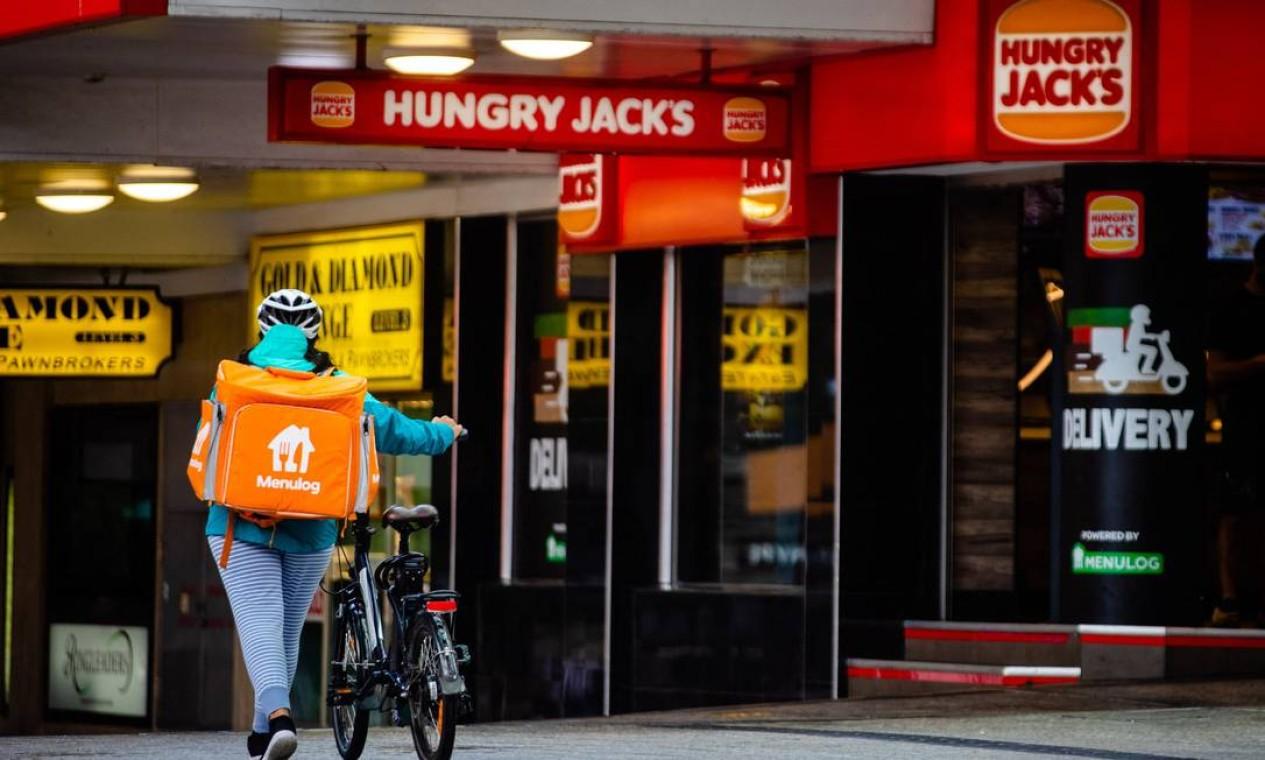 Entrega empurra bicicleta diante de vitrines de lojas fechadas em Brisbane Foto: PATRICK HAMILTON / AFP