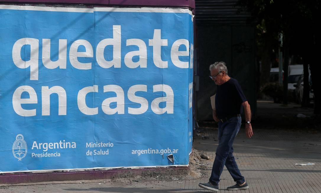 """Homem caminha em Buenos Aires em frente a cartaz que diz: """"Fique em casa"""" Foto: AGUSTIN MARCARIAN / Reuters"""