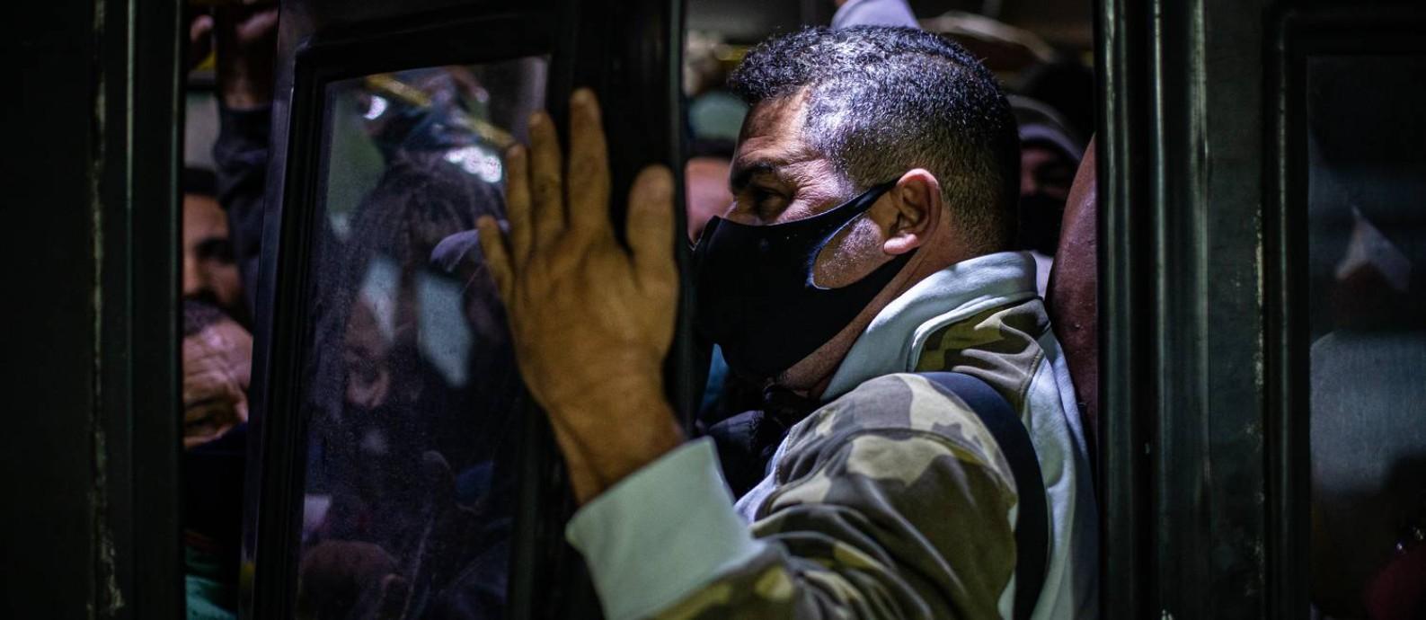Em ônibus lotado, passageiro viaja segurando a porta no BRT TransOeste Foto: Hermes de Paula / Agência O Globo