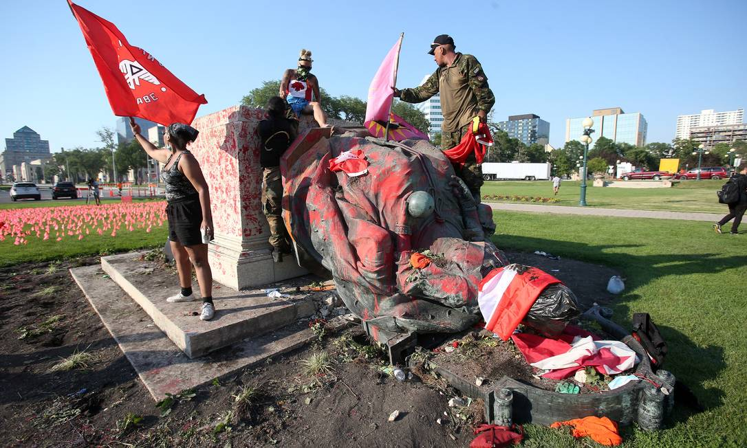 Manifestantes exibem bandeiras após derrubada de estátua da rainha Victoria em Winnipeg, no Canadá Foto: SHANNON VANRAES / REUTERS
