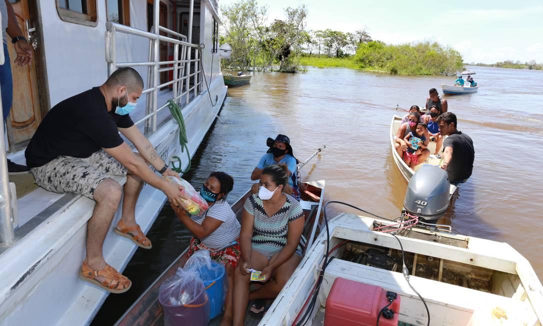 Cestini essenziali vengono distribuiti in barca ai residenti isolati della comunità di Santa Luzia, Erranduba Foto: Euzivaldo Queiroz / Agência O Globo