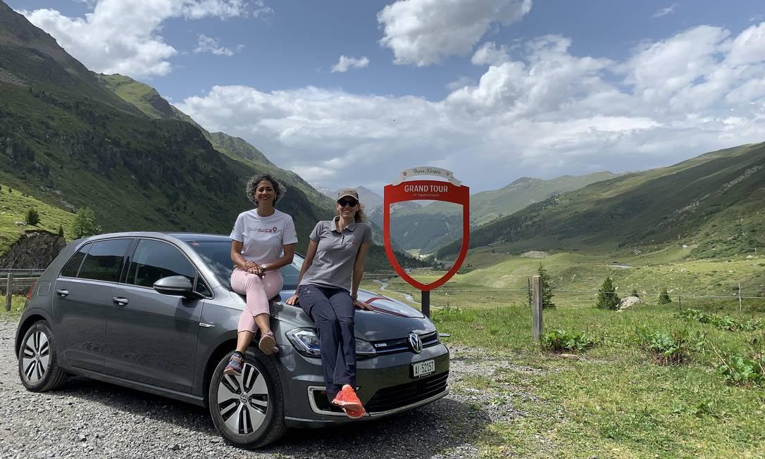 As guias de turismo brasileiras Magali Albisser e Luci de Lima Strijbis no Passo Flüela, com o carro elétrico, que as duas usaram para viajar pela Suíça Foto: Acervo pessoal
