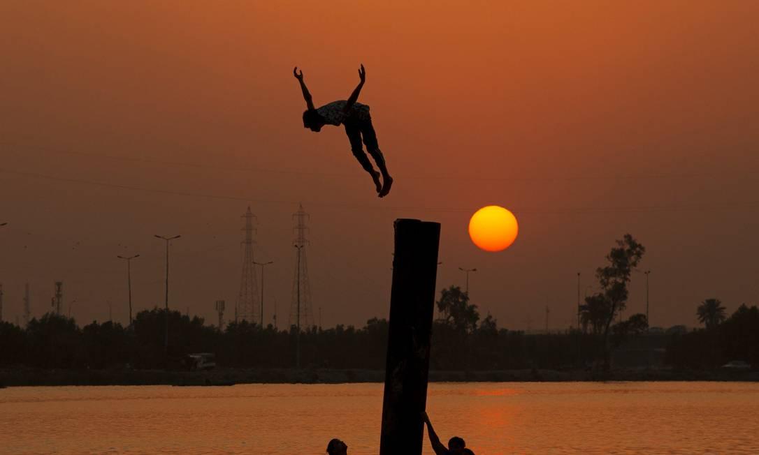 Jovens iraquianos mergulham no rio Shatt Al-Arab, perto do porto de Maqil, em meio a onda de calor na cidade de Basra, no sul do Iraque Foto: HUSSEIN FALEH / AFP