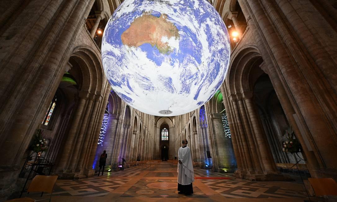 Membro do clero posa sob a instalação do artista britânico Luke Jerram 'Gaia', uma réplica de 7 metros do planeta Terra, suspensa na nave da Catedral de Ely em Ely, Cambridge Foto: OLI SCARFF / AFP