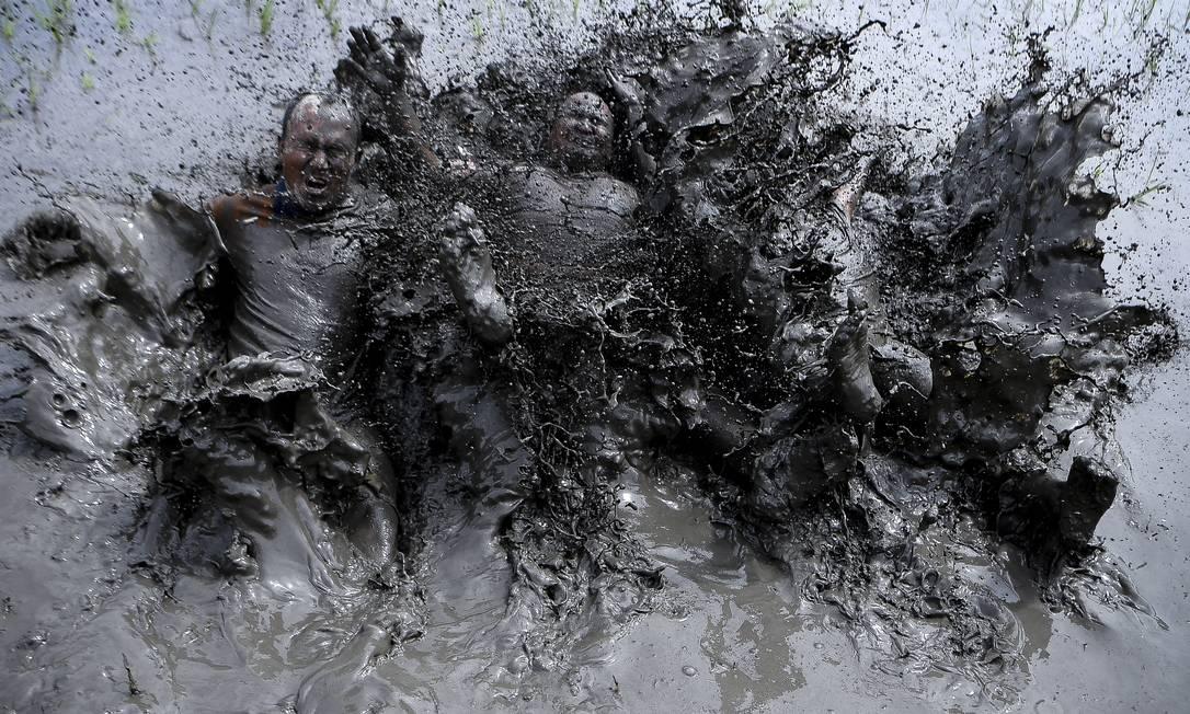 Agricultores cobertos de lama brincam em um arrozal durante o