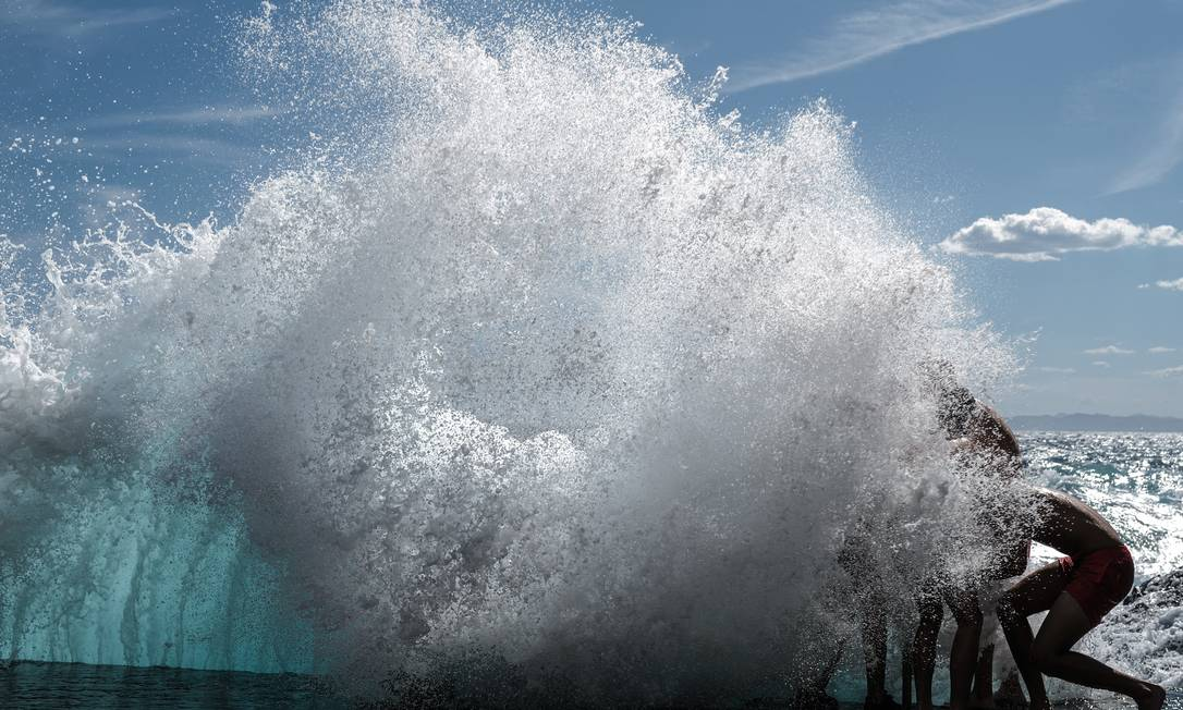 Banhistas brincam nas ondas do mar Mediterrâneo, em Nice, na França Foto: VALERY HACHE / AFP