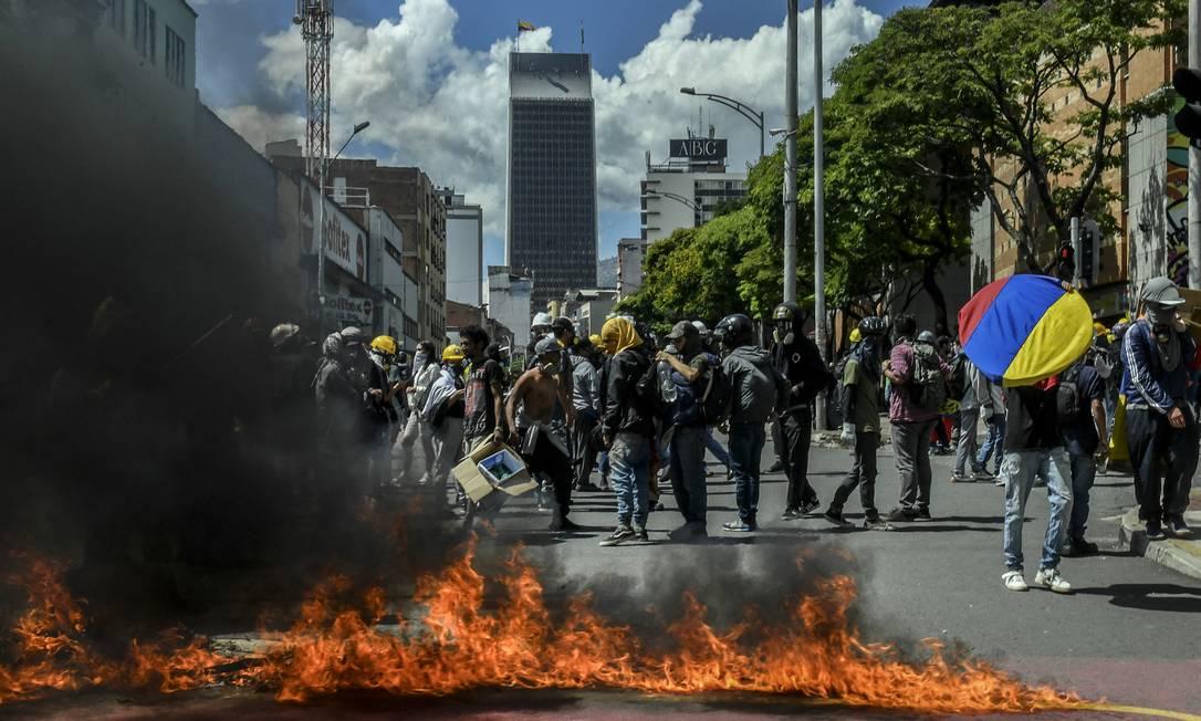 Manifestantes bloqueiam uma rua durante um protesto contra o governo em Medellín, Colômbia Foto: JOAQUIN SARMIENTO / AFP