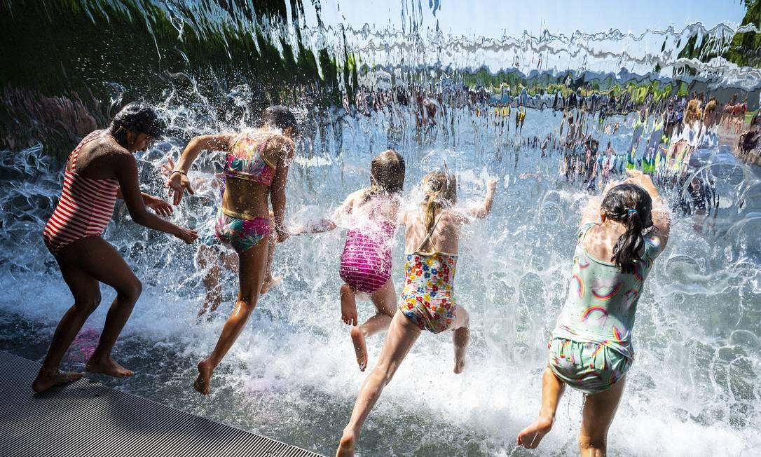 Meninas mergulham na cachoeira de um parque em Washington, durante onda de calor que atinge grande parte dos Estados Unidos Foto: JIM WATSON / AFP