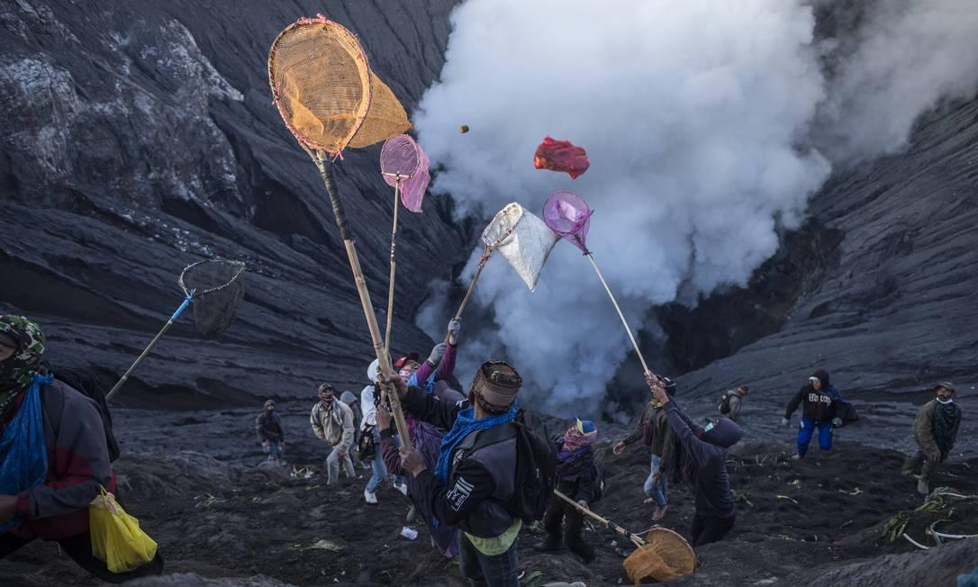 Pessoas tentam pegar oferendas lançadas por membros da tribo Tengger no cume do vulcão ativo Monte Bromo, em Probolinggo, província de Java Oriental Foto: JUNI KRISWANTO / AFP