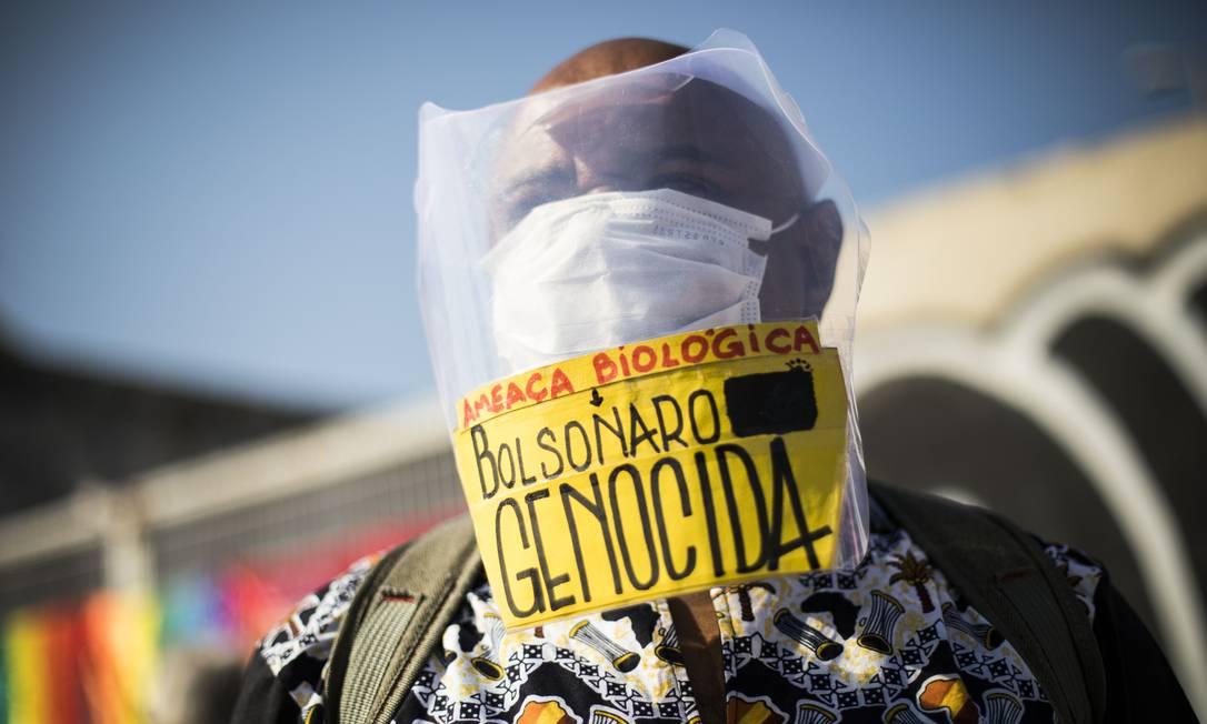 Homem usando máscara de proteção e escudo facial protesta contra o presidente Bolsonaro, no Centro do Rio Foto: Guito Moreto / Agência O Globo