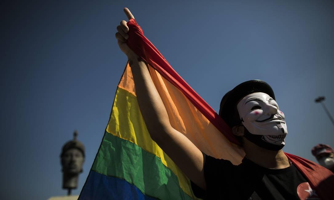 Manivestante segura bandeira arco-íris durante protesto contra o governo Bolsonaro no Centro do Rio Foto: Guito Moreto / Agência O Globo