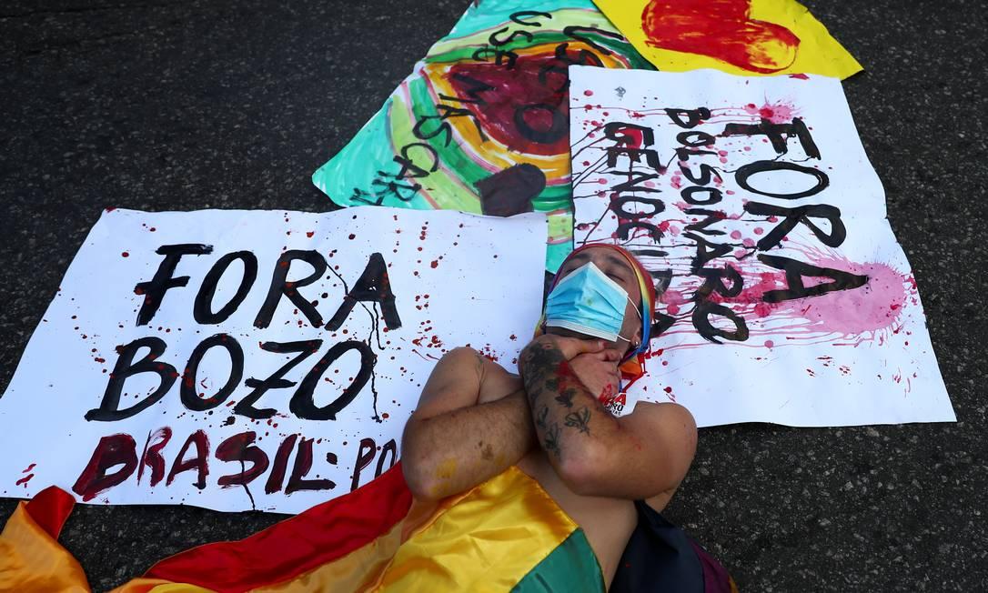 Manifestante se deita sobre cartazes pedindo a saída de Bolsonaro da presidenência durante ato no Rio de Janeiro Foto: PILAR OLIVARES / REUTERS
