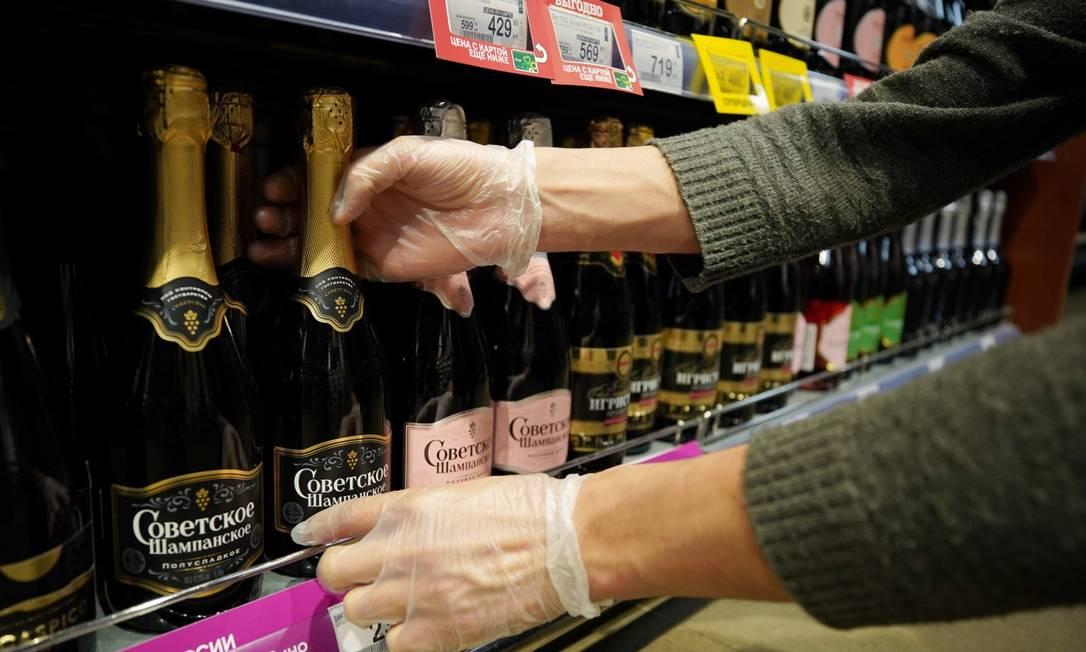 Um funcionário num mercado em Moscou arruma garrafas de vinho na prateleira Foto: TATYANA MAKEYEVA / REUTERS