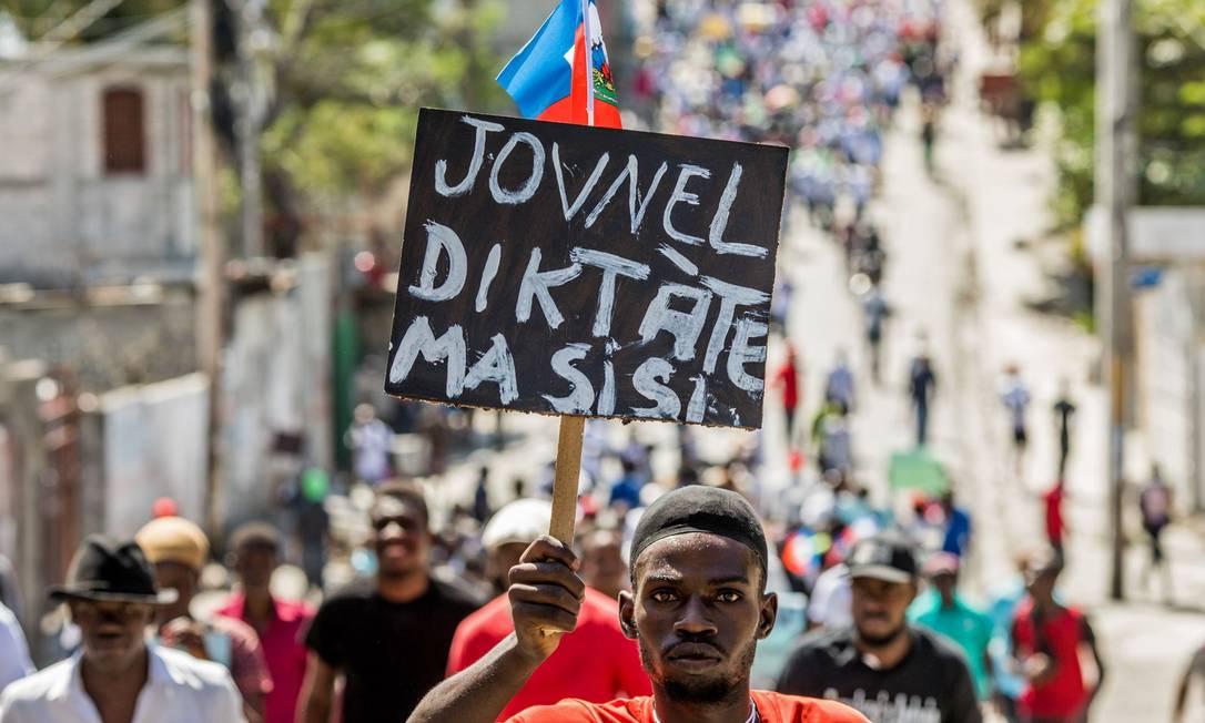 Manifestantes marcham em Porto Príncipe para protestar contra o governo do presidente Jovenel Moise. Milhares de pessoas saíram às ruas em 14 de fevereiro de 2021 para denunciar uma nova ditadura no Haiti e o apoio da comunidade internacional ao presidente Jovenel Moise Foto: Valerie Baeriswyl / AFP