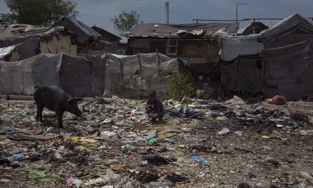 Criança é flagrada defecando sobre lixo ao lado de barracos da favela Cite Soleil, em Porto Principe Foto: Daniel Marenco / Agência O Globo - 28/08/2017