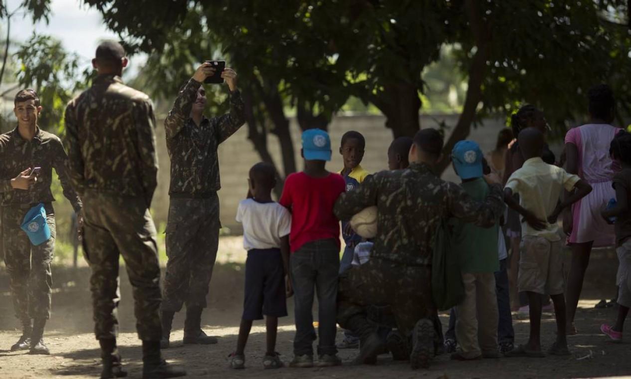 Militares brasileiros tiram fotos com crianças da Escola Sagrado Coração de Jesus, em Porto Principe. Missão de paz da ONU durou 13 anos no país Foto: Daniel Marenco / Agência O Globo - 29/08/2017