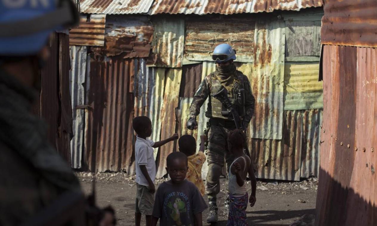 Militar do exército interage com criança na favela de Cite Solei Foto: Daniel Marenco / Agência O Globo - 30/08/2017