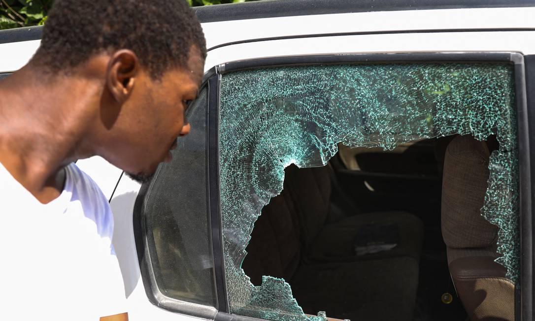 Homem olha para buracos de bala em um carro do lado de fora da residência presidencialem Porto Príncipe, Haiti. O presidente Jovenel Moise foi assassinado e sua esposa ferida Foto: VALERIE BAERISWYL / AFP