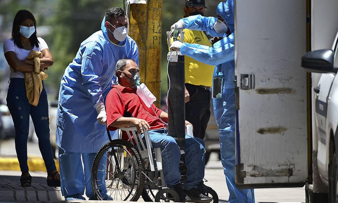 Profissional de saúde do Comitê Permanente de Contingência (Copeco) dá oxigênio a uma mulher infectada com COVID-19 no Hospital General San Felipe em Tegucigalpa, Honduras Foto: ORLANDO SIERRA / AFP