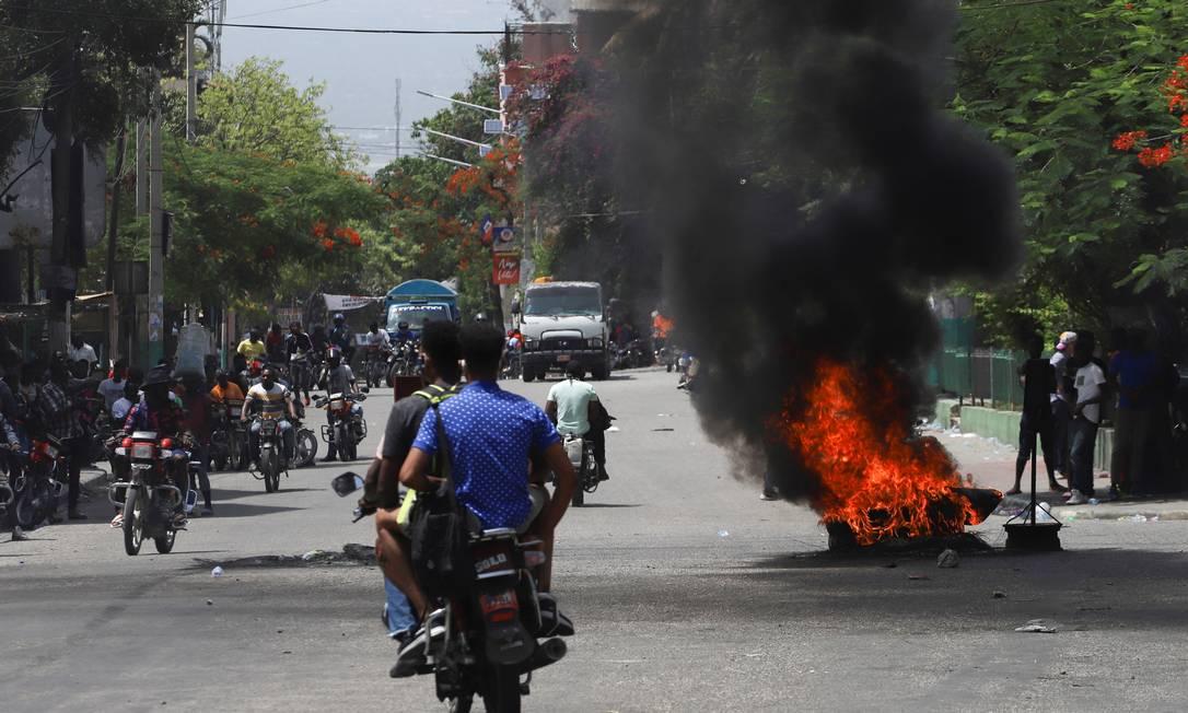 Pessoas passam ao lado de pneus em chama em Porto Príncipe Foto: STRINGER / REUTERS