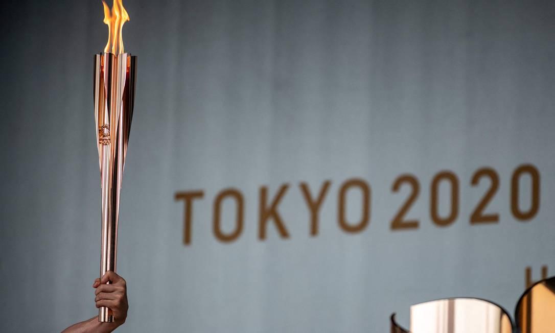 TOPSHOT - Um portador da tocha segura uma tocha olímpica durante a cerimônia de acendimento da chama olímpica em Machida Shibahiro, no primeiro dia do revezamento da tocha em Tóquio em 9 de julho de 2021. (Foto de Philip FONG / AFP) Foto: PHILIP FONG / AFP