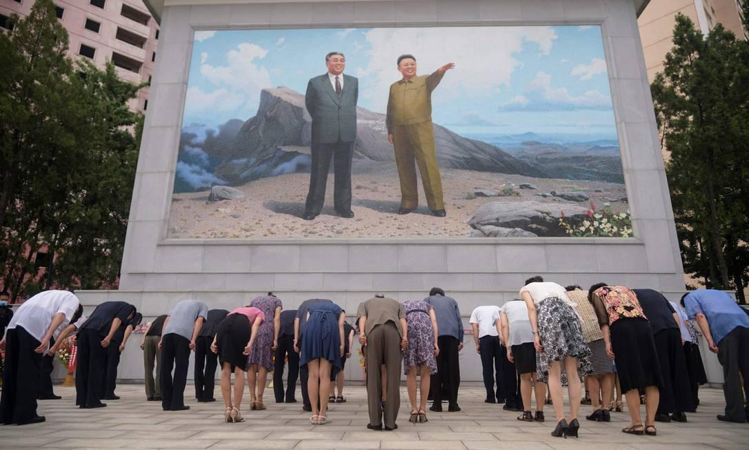 Pessoas se curvam diante de um mosaico de retratos dos falecidos líderes norte-coreanos Kim Il Sung e Kim Jong Il, na encruzilhada Dongmun, no distrito de Daedonggang de Pyongyang, por ocasião do 27º aniversário da morte de Kim Il Sung Foto: KIM WON JIN / AFP