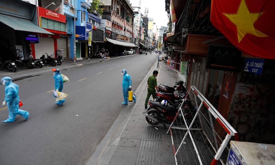 Trabalhadores médicos coletam amostras de teste de residentes passam pela cidade de Ho Chi Minh, no primeiro dia em que o governo impôs bloqueio de duas semanas como medida preventiva para impedir a disseminação do coronavírus COVID-19, no Vietnã Foto: HUU KHOA / AFP
