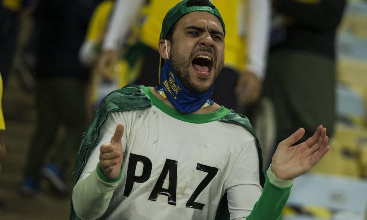 Torcedor com máscara de proteção no queixo grita da arquibancada antes da final da Copa América entre Brasil e Argentina, no Maracanã Foto: Guito Moreto / Agência O Globo