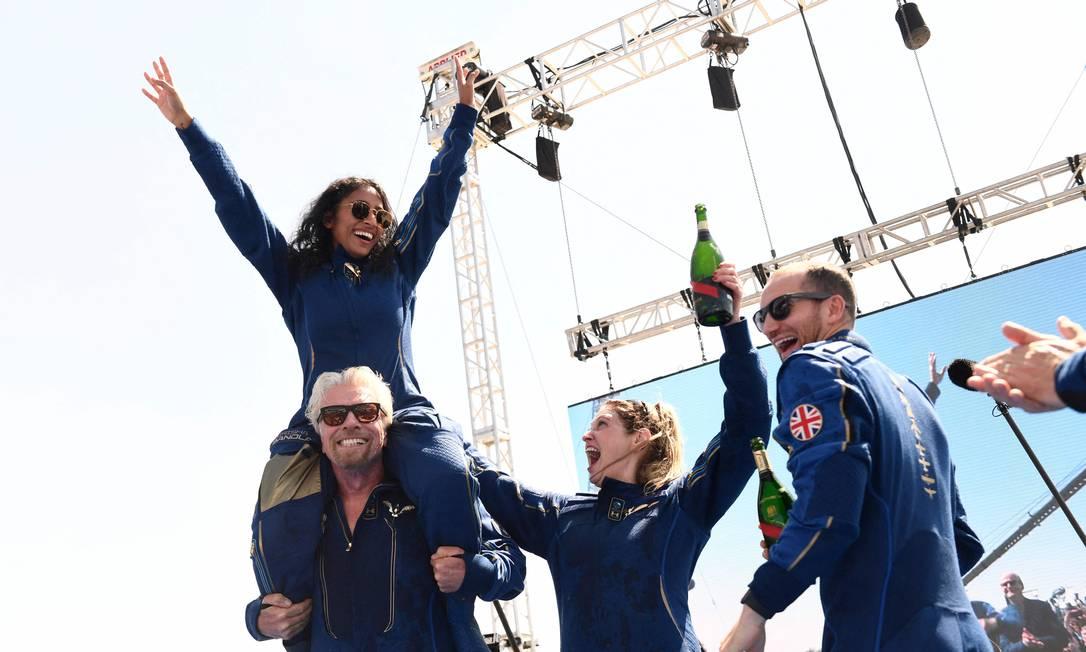 Richard Branson carga a la vicepresidenta de Virgin Galactic, Sirisha Bandla, sobre sus hombros y celebra con el equipo Foto: PATRICK T.FALLON / AFP