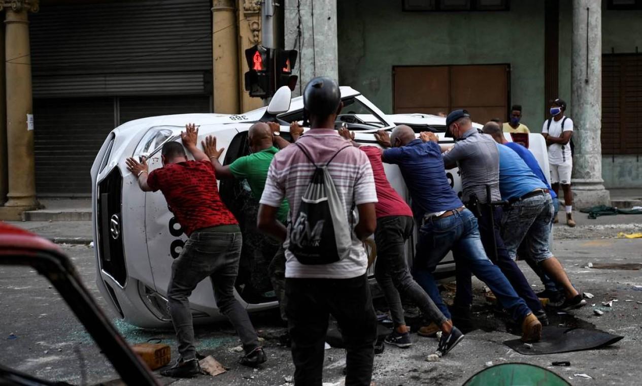 Mnifestantes viram um carro durante protesto contra o presidente cubano, Miguel Díaz-Canel, em Havana Foto: YAMIL LAGE / AFP