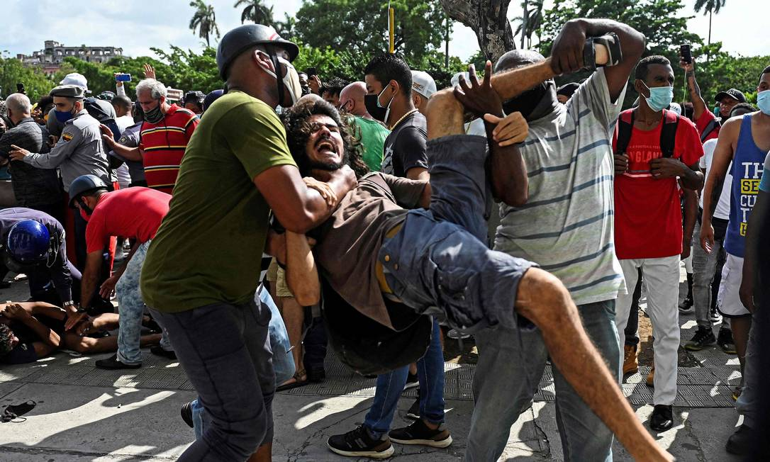 Homem é preso durante uma manifestação contra o governo do presidente cubano. As manifestações começaram pela manhã de domingo, na cidade de San Antonio de los Baños, a sudoeste de Havana Foto: YAMIL LAGE / AFP