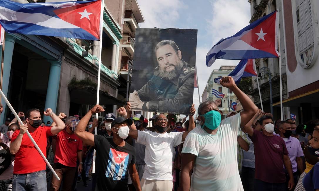 Apoiadores do governo exibem uma fotografia do falecido presidente cubano Fidel Castro durante protestos contra e em apoio ao governo. O presidente Miguel Díaz-Canel convocou 'revolucionários' a irem às ruas em defesa do governo Foto: ALEXANDRE MENEGHINI / REUTERS