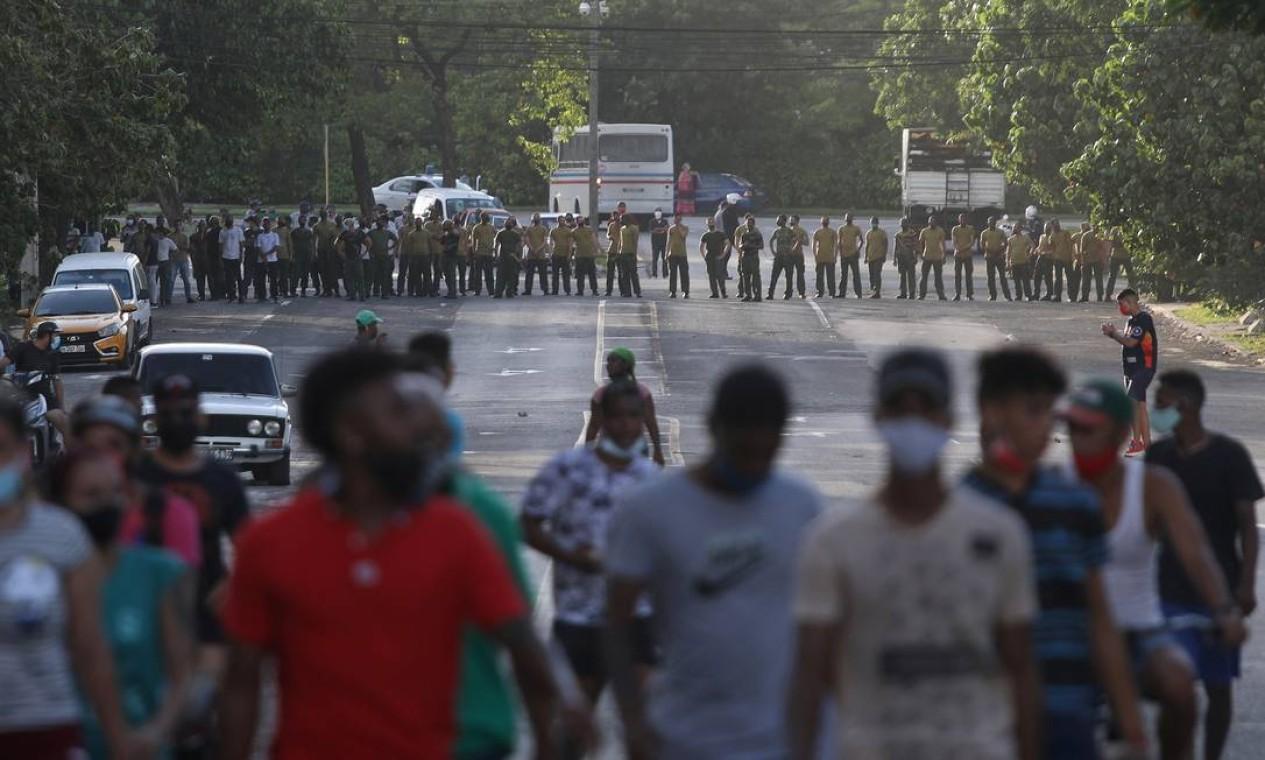 Manifestantes se afastam de soldados do Exército que bloqueiam uma estrada durante protestos que levaram opositores e apoiadores do governo às ruas de Havana, Cuba Foto: ALEXANDRE MENEGHINI / REUTERS