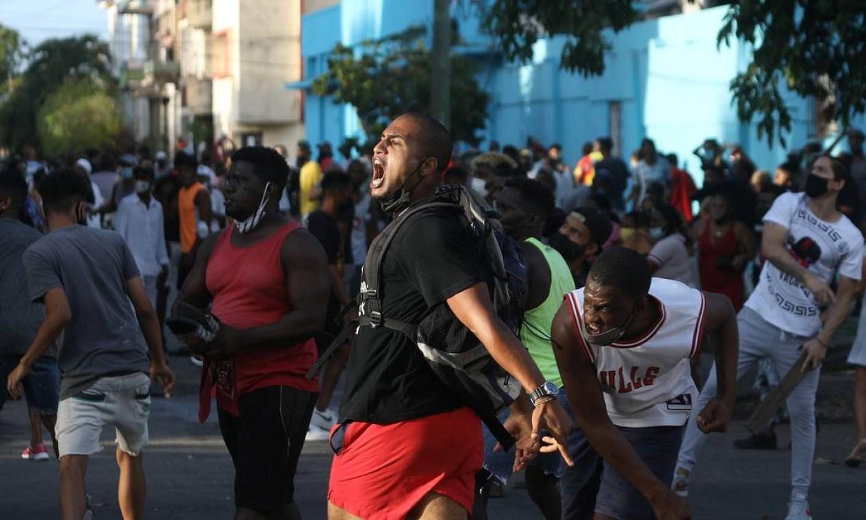 Manifestantes gritam palavras de ordem e atiram objetos contra força policial durante um protesto Foto: ALEXANDRE MENEGHINI / REUTERS