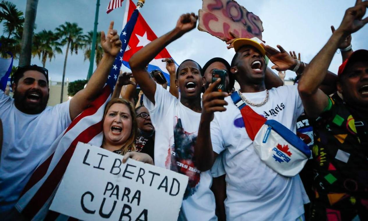 """Mulher exibe cartaz com os dizeres """"Liberdade para Cuba"""", enquanto outras pessoas protestam com bandeiras nacionais de Cuba e dos Estados Unidos durante um ato contra o governo cubano, em Miami, nos EUA Foto: EVA MARIE UZCATEGUI / AFP"""