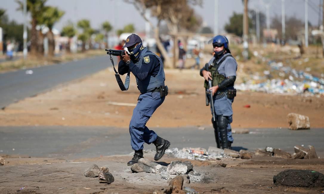 Membro dos Serviços de Polícia da África do Sul confrontam saqueadores após saques e vandalismo fora do Lotsoho Mall, em Katlehong, a leste de Joanesburgo Foto: PHILL MAGAKOE / AFP