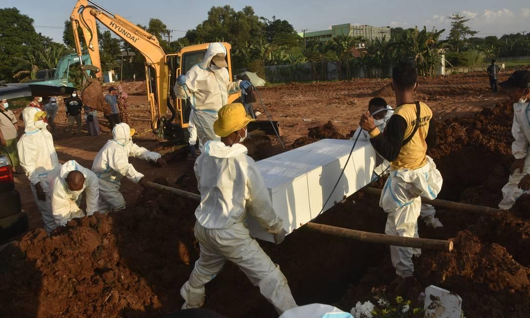 Coveiros carregam caixão para sepultamento em um cemitério em Bekasi, enquanto a Indonésia enfrenta um surto causado pela variante Delta da Covid-19 Foto: REZAS / AFP