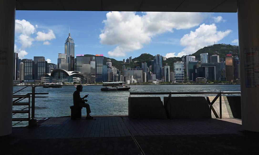 Mulher ouve seu rádio portátil perto do porto de Victoria Harbour, em Hong Kong Foto: PETER PARKS / AFP
