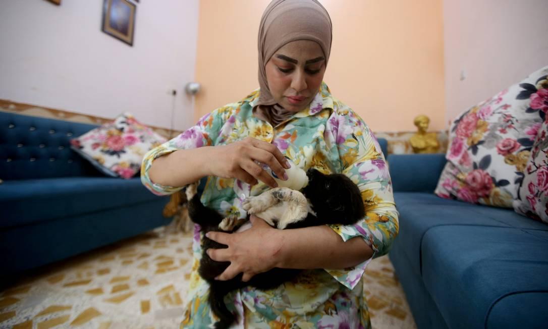 Zainab Al-Obeidy, que montou um abrigo para cães abandonados, alimenta um filhote em sua casa em Amarah, Iraque Foto: ESSAM AL-SUDANI / REUTERS