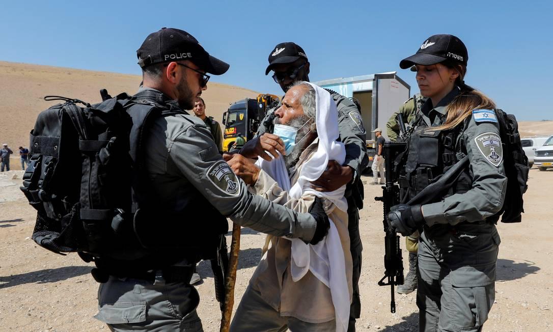 Homem palestino briga com membros da polícia de fronteira israelense enquanto esta confisca uma clínica de saúde em Yatta, na Cisjordânia ocupada por Israel Foto: MUSSA ISSA QAWASMA / REUTERS