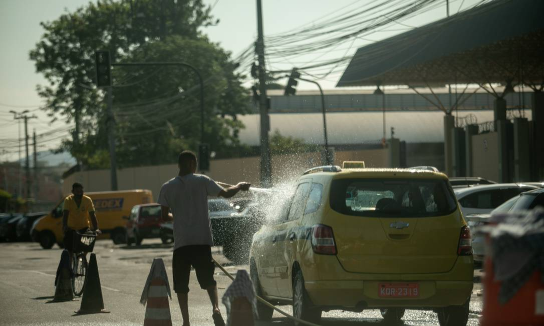 Mau exemplo: lava-jato no meio da pista da Rua Leopoldo Bulhões, em Benfica, usa água desviada de tubulação da Cedae Foto: Brenno Carvalho / Agência O Globo